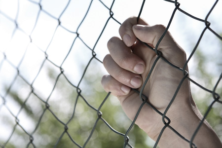Male Hand Holding on to Fence Stock Photo - 64728355