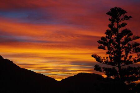 ady break fire in the sky against black mountain silhouette Stock Photo