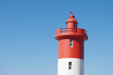 Lighthouse at Unhlanga Rocks in Durban South Africa painted a distinct red and white and managed by the Oyster Box Hotel since 1954