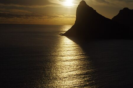 Eerie sunset showing streak of light over ocean with black mountain silhouette of the Sentinel in Hout Bay South Africa