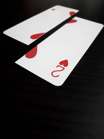 Close up of a two of hearts card split down the middle with shallow DOF photo