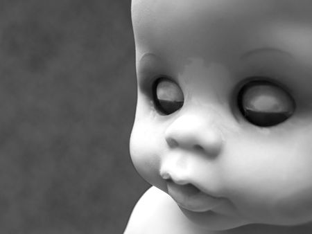 Portrait of an old worn doll in black and white photo