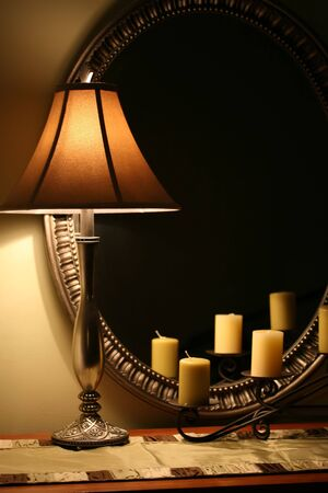 A cozy interior still life with lamp, candles and mirror