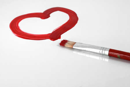 A red painted heart with paintbrush on white