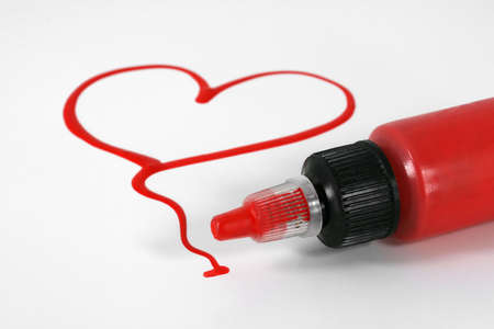 A red painted heart with paint bottle on white