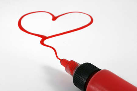 A red painted heart with paint bottle on white photo
