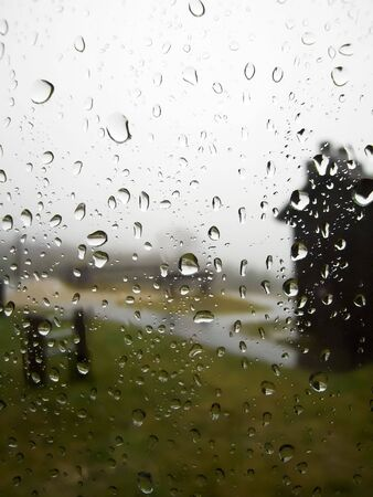A rainy day scene through a window with raindrops