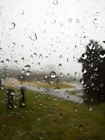 A rainy day scene through a window with raindrops photo