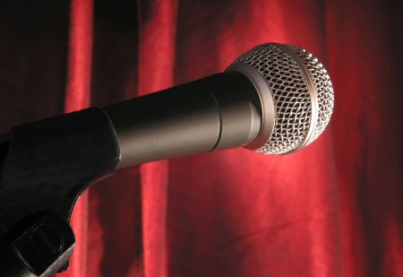 A microphone in the spotlight with a red stage curtain