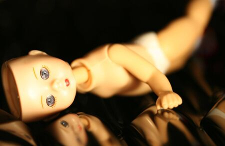 flaw: A doll with missing parts posed on a reflecting black background