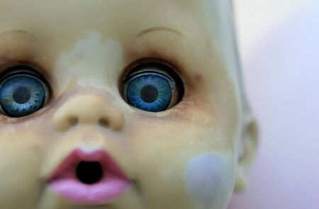 A close up of an old deteriorating doll