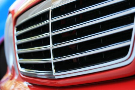 A close up of a red sports car grill