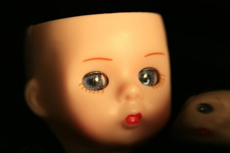 A close up of a dolls head with reflection in black background