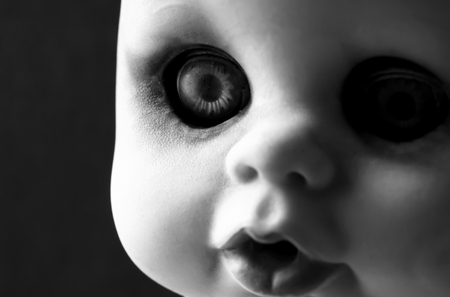 A black and white portrait of an old scary doll