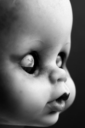 Moody black and white photo of an old dolls face