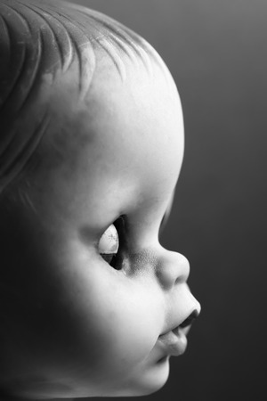 A black and white profile of a doll with closed eyes