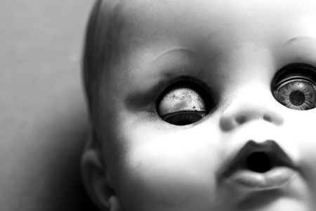 Close up of a scary doll with one eye closed and one eye open