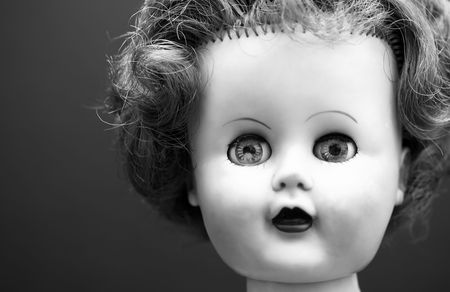 A black and white portrait of an old doll