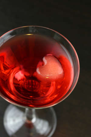 A red martini cocktail with a heart shaped ice cubes photo