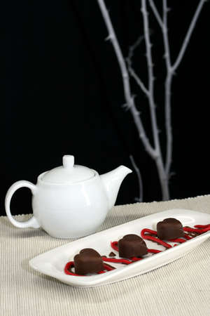 Teapot and chocolates with a minimal table setting