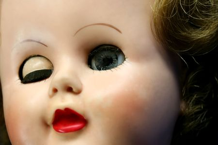 Close up of a doll face with one eye closed