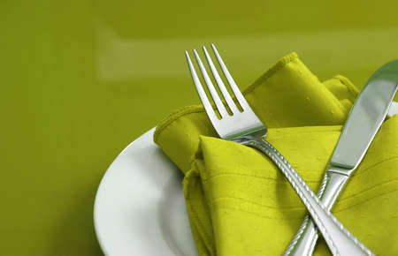 An elegant holiday table setting with fork, knife and napkin