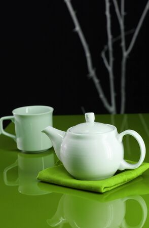 A modern table setting with a teapot and cup