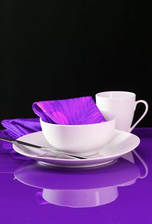 A modern table setting with white dishes on a purple background