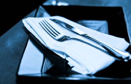 A soft blue-toned image of a table setting with plate, napkin and utensils photo
