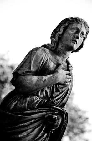 deteriorating: A black and white image of an angel statue in prayer