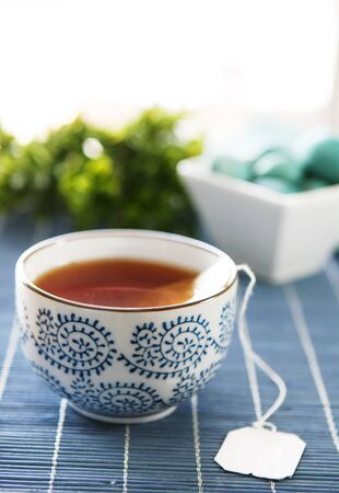teabag: a cup of healthy green tea on blue tabletop