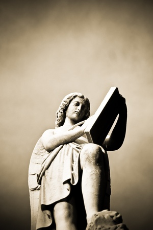 A statue of an angel reading scripture shot from below