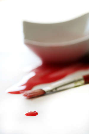 spilled paint: A drop of red paint with paintbrush and spilled paint in background