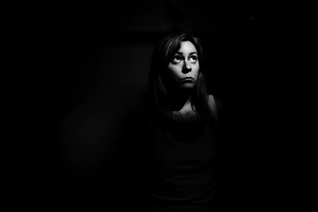 girl looking up: A woman trapped in the dark looking up into a shaft of light Stock Photo