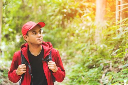 Młody azjatycki podróży przystojny mężczyzna wędrówki w lesie i górach cieszyć spacery w przyrodzie na świeżym powietrzu. Obraz koncepcji kempingu stylu życia, podróży, turystyki pieszej lub rekreacji z miejsca na kopię. Zdjęcie Seryjne