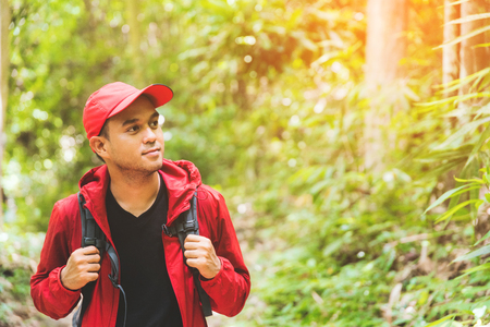 Young asian travel handsome man hiking in forest and mountain enjoy walking in nature outdoors. Image of lifestyle camping,travel,hiking or recreation concept with copy space. Stock Photo
