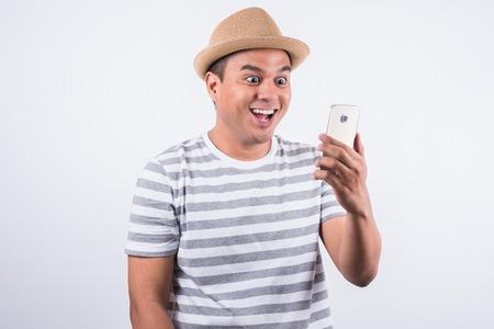 Joven asiático con sombrero mirando smartphone y se siente conmocionado