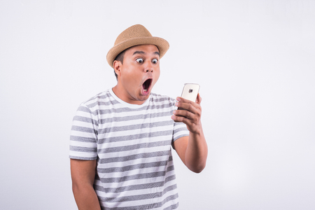 Young asian man with hat looking at smartphone and feels shocked