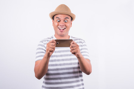 Surprised and shocked asian man looking smartphone Stock Photo