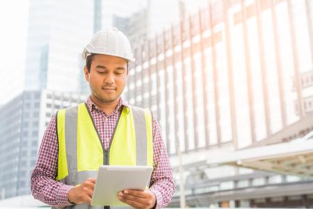 Ingeniero con casco sostiene una tableta. Concepto de gerente de construcción.