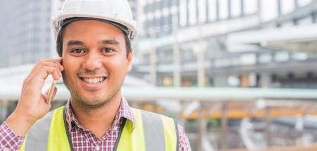 Junge asiatische Bauingenieurwesen telefonieren am Baugebäudehintergrund Standard-Bild