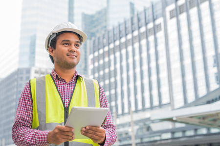 Young handsome asian civil engineer holding tablet looking forward and thinking, planning on construction building background. Archivio Fotografico