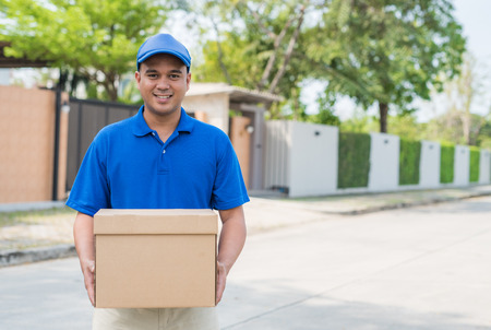 Blue delivery man holding the parcel cardboard box in front of house Banco de Imagens