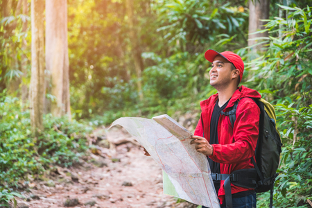 Young asian travel handsome man hiking in forest and mountain enjoy walking in nature outdoors. Standard-Bild