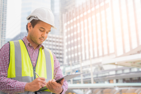 Young civil engineer reading work on clipboard for planning construction building.
