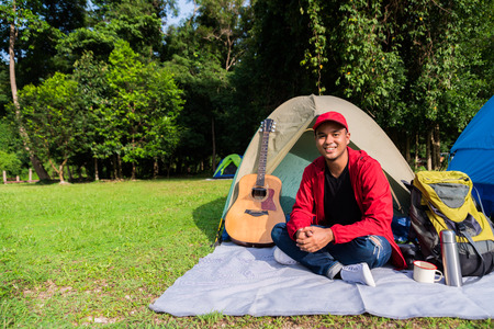 Young asian tourist backpacker sitting in a tent camping in Forest. Image of camping,travel,lifestyle or recreation concept.
