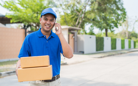 Blue Delivery man holding parcel cardboard box and talking on phone.