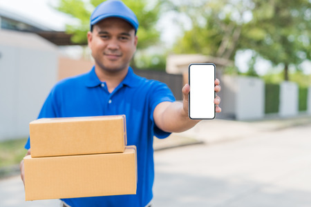 Blue Delivery man holding parcel cardboard box and showing smartphone.