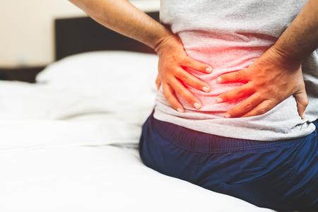 Hombre que sufre de dolor de espalda en el dormitorio. Foto de archivo