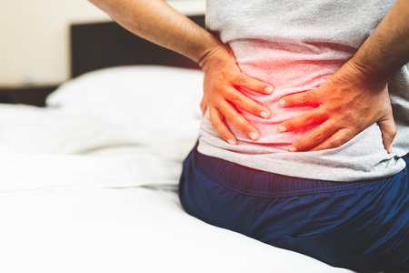 Mann leidet unter Rückenschmerzen im Schlafzimmer. Standard-Bild